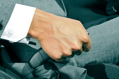 Man in suit pulling the hand brake of a car Royalty Free Stock Photo