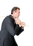 Man in suit pulling a rope Royalty Free Stock Image
