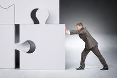 Man in suit pushing grey puzzle piece Royalty Free Stock Photo