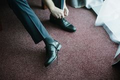 A man in a suit puts shoes on his feet royalty free stock photo