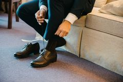 A man in a suit puts shoes on his feet stock photo