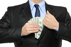 Man in a suit putting money in his pocket Stock Photo