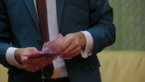 A man in a suit recounts money Ukrainian Hryvnia. Footage of a groom counting and putting in order money in his hands stock video