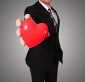 Man in suit with red heart Stock Images