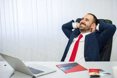 Man in a suit with a red tie is happy in office stock image