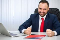 successfulity man in a suit with a red tie is happy in the office royalty free stock photography
