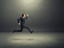 Man in suit running fast in the dark room Stock Photos