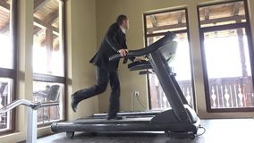 Man with suit running on gym machine, work break, running to succes stock video