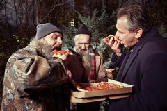 Man in suit sharing pizza with two hungry homeless men Stock Photos