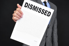Man in suit showing a document with the text dismissal. A young caucasian man in gray suit showing a document with the text dismissal written in it on a black Stock Photos
