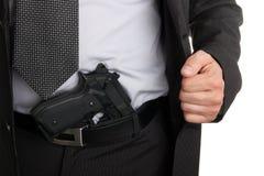 Man in suit showing gun tucked in pants Stock Image