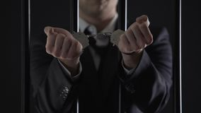 Man in suit showing hands in handcuffs behind bars, bribery, financial fraud