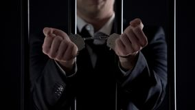 Man in suit showing hands in handcuffs behind bars, bribery, financial fraud stock images