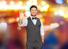 Man in suit showing ok sign over night city lights. Fashion, style and gesture concept - happy man in festive suit showing ok hand sign over night city lights Royalty Free Stock Photo