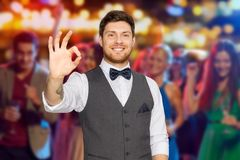 Man in suit showing ok sign over night club party Stock Photography