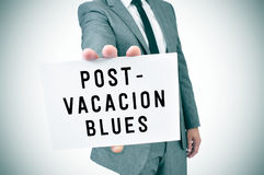 Man in suit shows a signboard with the text post-vacation blues, Stock Photo
