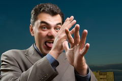 Man in a suit shows tongue Stock Photography