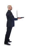 Man in suit side view laptop. Man presenting laptop in side view on white background Royalty Free Stock Photos