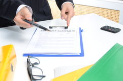 Man in suit signing documents. On the table Stock Images