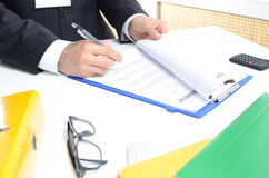 Man in suit signing documents. On the table Royalty Free Stock Photo