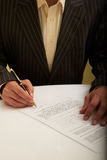 Man in a suit signs the document Stock Photos