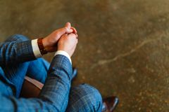 Man in a suit sits with his hands on his knees. Putting your hands together. Shoot of a man in a suit sitting with his hands folde. D together with space for royalty free stock image