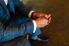 Man in a suit sits with his hands on his knees. Putting your hands together. Shoot of a man in a suit sitting with his hands folde. D together with space for royalty free stock images