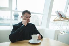 A man in a suit sits in a stylish restaurant at the table near the window and communicates on the phone Stock Photography