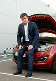Man in suit sitting on broken car with open hood Royalty Free Stock Photography