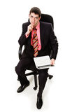 Man in a suit, sitting in a chair, laptop. Royalty Free Stock Photo
