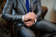 Man in a suit sitting in a chair and puts cufflinks Stock Image