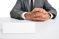 Man in suit sitting in a desk with a blank signboard in front of Stock Photos