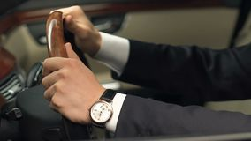 Man in suit sitting on driver place and holding steering wheel, new car purchase. Stock footage stock video