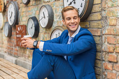 Man in suit sitting near wall with clocks Royalty Free Stock Image