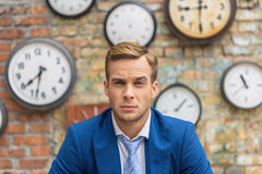 Man in suit sitting near wall with clocks Royalty Free Stock Images