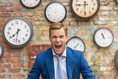 Man in suit sitting near wall with clocks Stock Photos