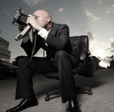 Man in a suit sitting and photographing Royalty Free Stock Images