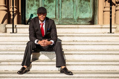 Man in suit sitting on steps. A young man in a suit with a red tie and hat sitting down Stock Image