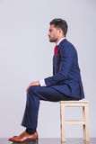Man in suit sitting in studio with hands on his knees. Side portrait on man in suit sitting in studio with hands on his knees royalty free stock photo
