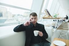 A man in a suit sitting at a table in a bright cafe near the window and talking on the phone. Stock Image