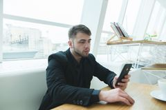 A man in a suit sitting at the table in a light cafe near the window and writing a message on his smartphone. Royalty Free Stock Images