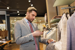 Man in suit with smartphone at clothing store Stock Photo
