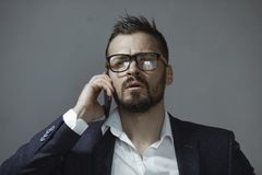 Man in Suit With a Smartphone. A handsome young businessman in suit and glasses talking on smartphone indoors against a gray background. Portrait of a bearded royalty free stock images