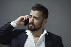 Man in Suit With a Smartphone. A handsome young businessman talking on smartphone indoors against a gray background. Portrait of a bearded concentrated man stock images