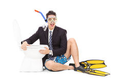 Man with suit and snorkel sitting by a toilet Royalty Free Stock Photo
