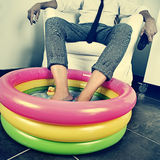 Man in suit soaking his feet in an inflatable water pool, with a Royalty Free Stock Photography