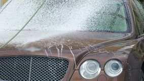 Man in suit sprinkling expensive car with soapy foam, carwash service, cleaning. Stock footage stock video footage