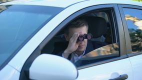 Man in suit spying from car using binoculars, private detective investigation. Stock footage stock video footage