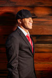 Man in suit standing against wall smiling. A young man in a suit with a red tie and hat standing against wood Stock Photo