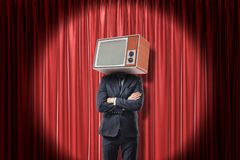 Man in suit standing with arms folded, with TV set instead head, in spotlight near red stage curtain. stock images